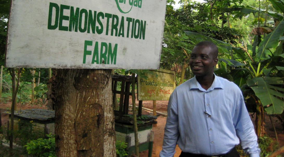Man stands by sign for demonstration farm in Ghana